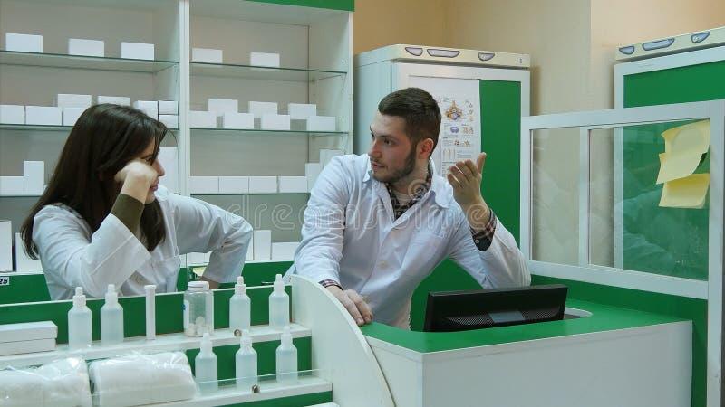 Κουρασμένη ομάδα του φαρμακοποιού που μιλά μαζί για το φάρμακο στο φαρμακείο, περιμένοντας το τέλος της ημέρας εργασίας στοκ φωτογραφίες