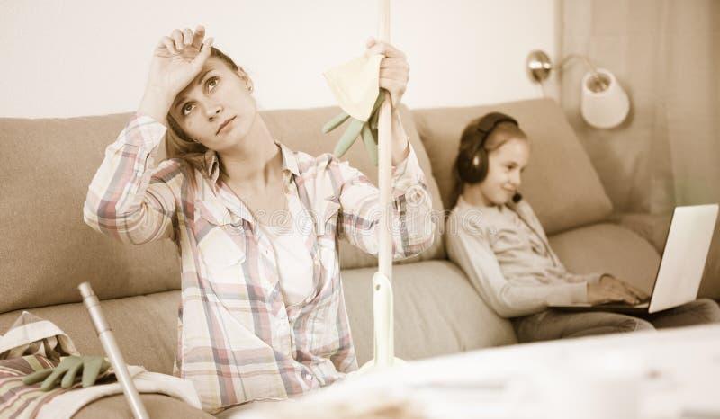 Κουρασμένη συνεδρίαση μητέρων με τη σφουγγαρίστρα στοκ εικόνα