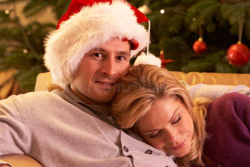 Κουρασμένη χαλάρωση ζεύγους μπροστά από το χριστουγεννιάτικο δέντρο στοκ φωτογραφία με δικαίωμα ελεύθερης χρήσης