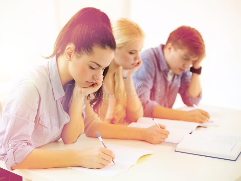 Κουρασμένοι σπουδαστές με τα σημειωματάρια στο σχολείο στοκ εικόνα