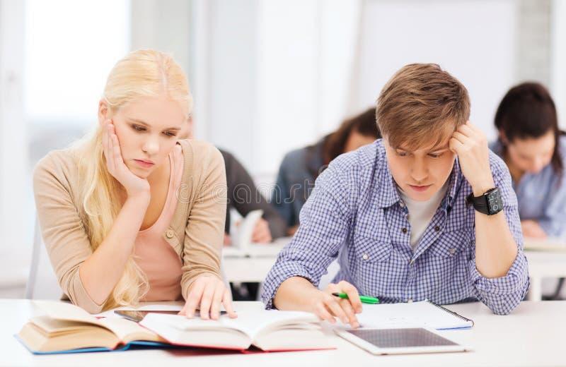 Κουρασμένοι σπουδαστές με το PC ταμπλετών, τα σημειωματάρια και τα βιβλία στοκ εικόνες