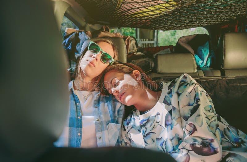Κουρασμένοι φίλοι γυναικών που κοιμούνται σε ένα οπίσθιο αυτοκίνητο καθισμάτων στοκ φωτογραφία με δικαίωμα ελεύθερης χρήσης