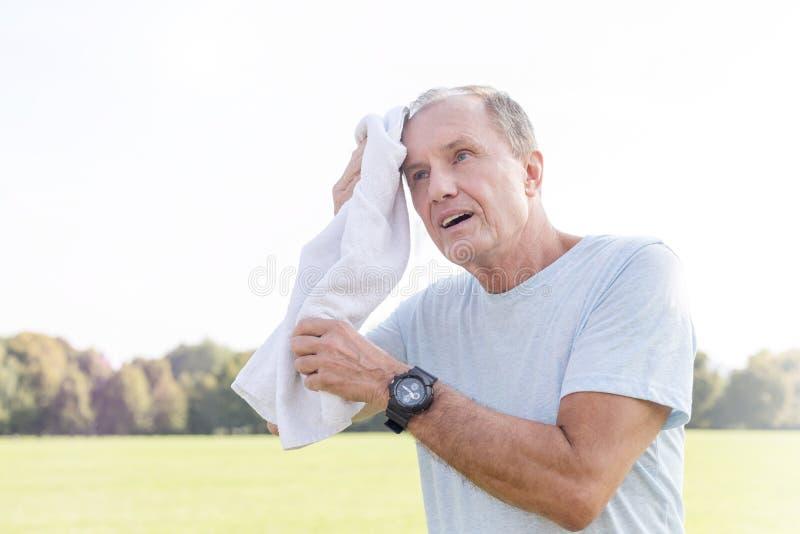 Κουρασμένος ανώτερος καθαρίζοντας ιδρώτας ατόμων μετά από το workout στο πάρκο στοκ φωτογραφίες