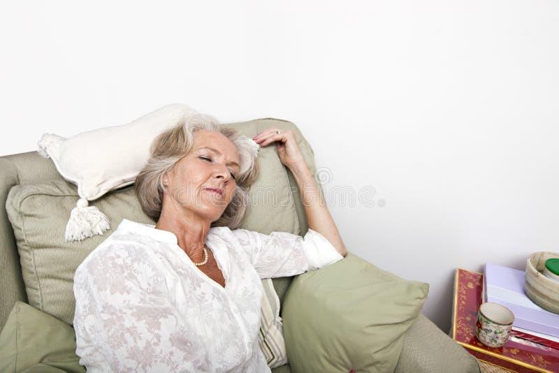 Κουρασμένος ανώτερος ύπνος γυναικών στην πολυθρόνα στο σπίτι στοκ φωτογραφίες