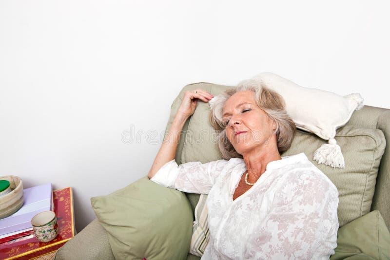 Κουρασμένος ανώτερος ύπνος γυναικών στην πολυθρόνα στο σπίτι στοκ φωτογραφίες με δικαίωμα ελεύθερης χρήσης