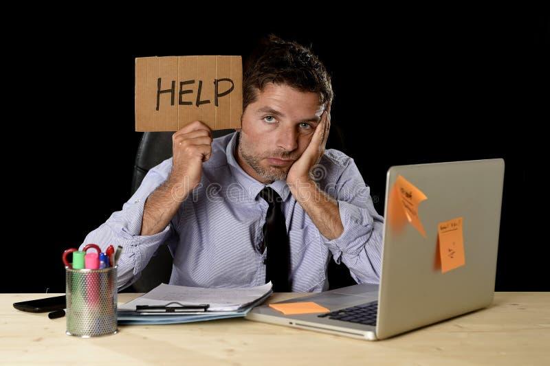 Κουρασμένος απελπισμένος επιχειρηματίας στην πίεση που εργάζεται στο σημάδι εκμετάλλευσης γραφείων υπολογιστών γραφείων που ζητά  στοκ εικόνες