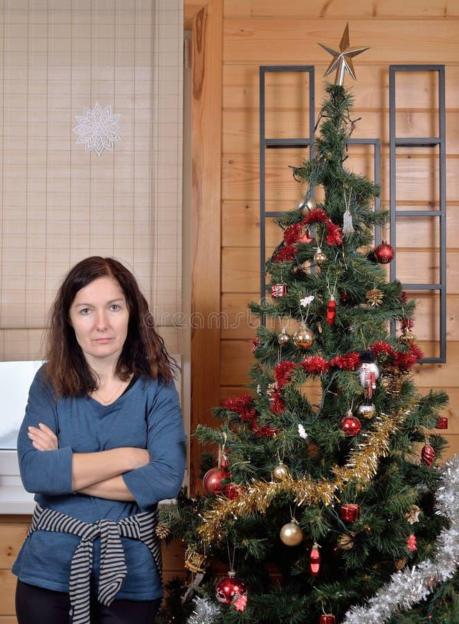 Κουρασμένος δύσπιστος της γυναίκας στο χριστουγεννιάτικο δέντρο στοκ εικόνες με δικαίωμα ελεύθερης χρήσης