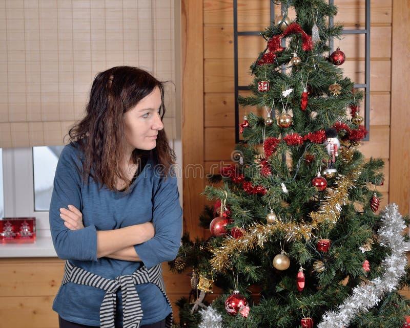 Κουρασμένος δύσπιστος της γυναίκας στο χριστουγεννιάτικο δέντρο στοκ φωτογραφία με δικαίωμα ελεύθερης χρήσης