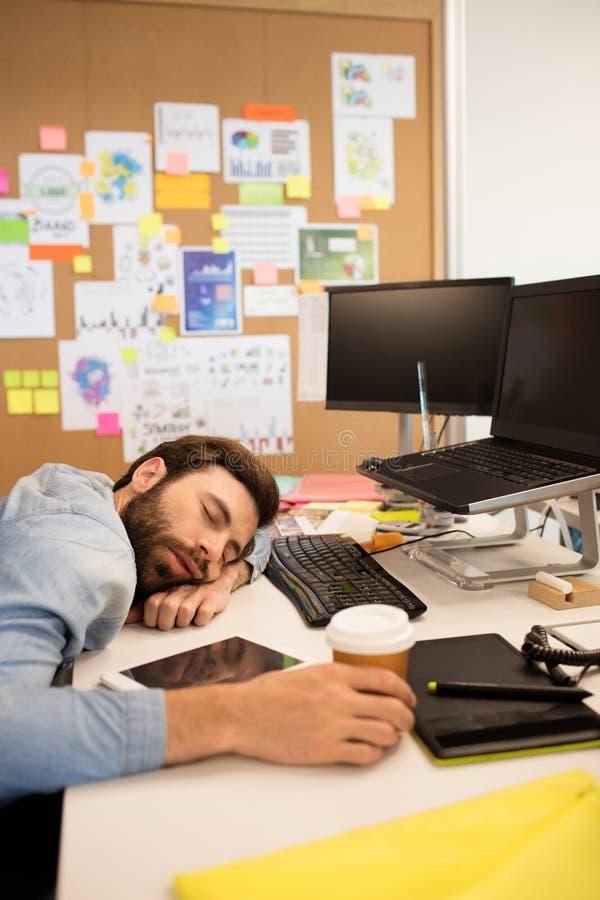 Κουρασμένος επιχειρηματίας κοιμισμένος στο δημιουργικό γραφείο στοκ φωτογραφία με δικαίωμα ελεύθερης χρήσης