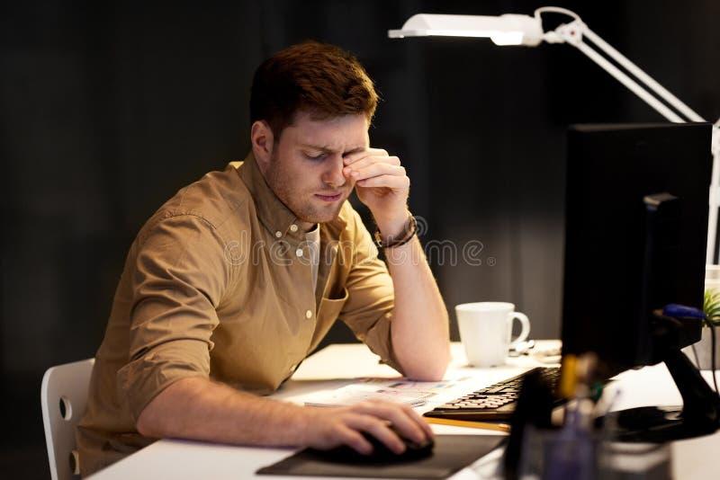 Κουρασμένος επιχειρηματίας που απασχολείται αργά τη νύχτα στο γραφείο στοκ εικόνες