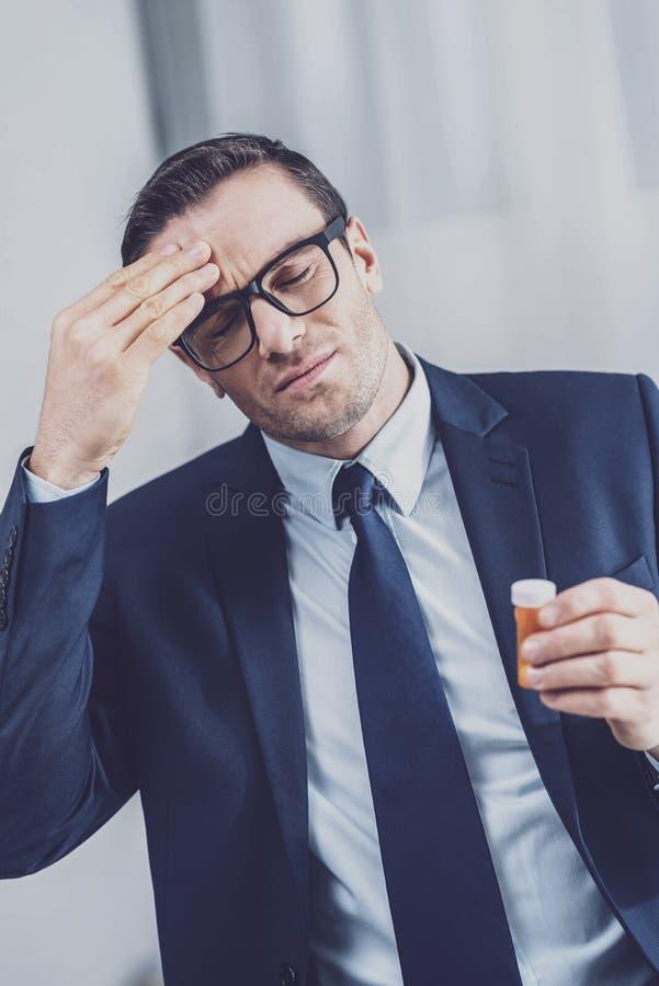 Κουρασμένος εργαζόμενος γραφείων που έχει έναν πονοκέφαλο στοκ φωτογραφία
