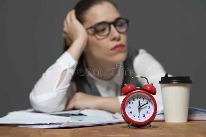 Κουρασμένος εργαζόμενος γραφείων στον πίνακα με τα έγγραφα και το κόκκινο ξυπνητήρι στοκ φωτογραφία
