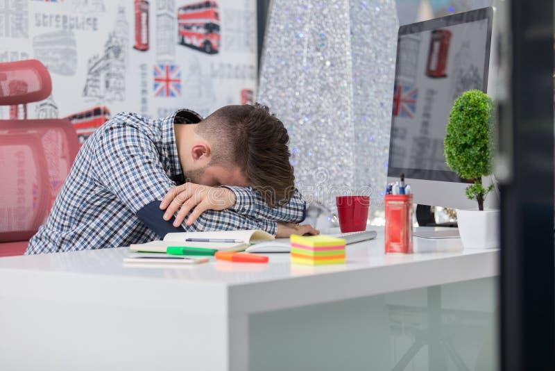 Κουρασμένος καταπονημένος ύπνος επιχειρηματιών πέρα από ένα γραφείο στην εργασία στο γραφείο του στοκ εικόνες
