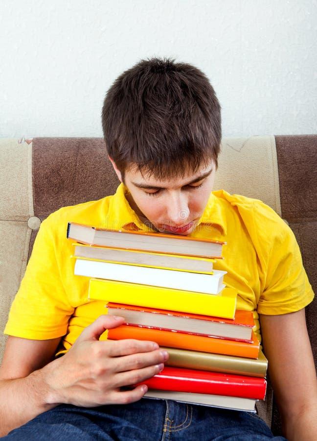 Κουρασμένος νεαρός άνδρας με τα βιβλία στοκ εικόνες