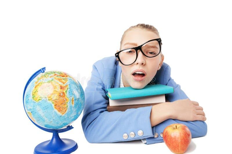 Κουρασμένος σπουδαστής με το σωρό των βιβλίων στοκ εικόνες