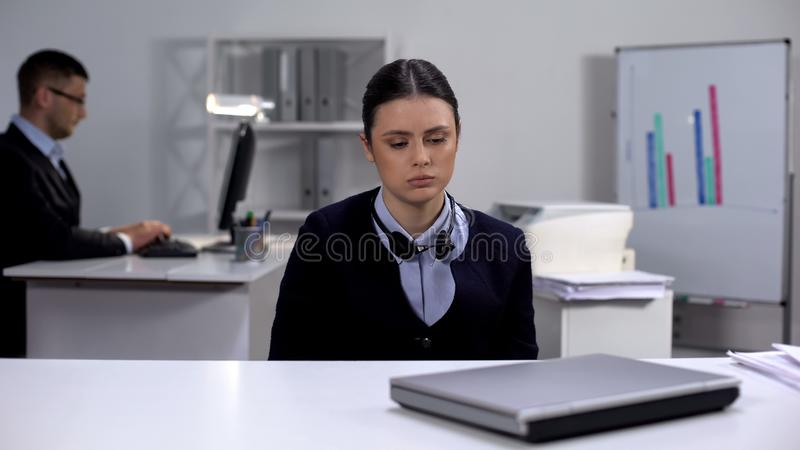 Κουρασμένος χειριστής τηλεφωνικών κέντρων που απογειώνει ακουστικά και κοιτάζει φορητό υπολογιστή, τέλος εργάσιμης ημέρας στοκ εικόνες