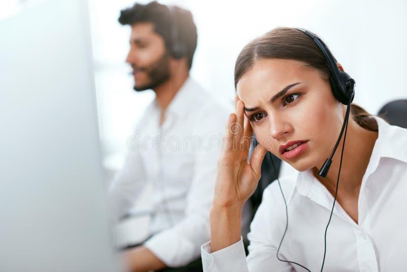 Κουρασμένος χειριστής τηλεφωνικών κέντρων στον εργασιακό χώρο στοκ εικόνες