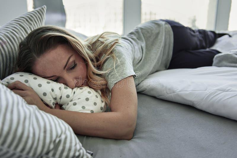 Κουρασμένος ύπνος γυναικών στην κρεβατοκάμαρα στοκ φωτογραφίες