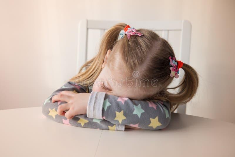 Κουρασμένος ύπνος μικρών κοριτσιών στον πίνακα στοκ φωτογραφία με δικαίωμα ελεύθερης χρήσης