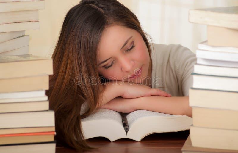 Κουρασμένος ύπνος σπουδαστών εντελώς πέρα από τα βιβλία στη βιβλιοθήκη στοκ φωτογραφία