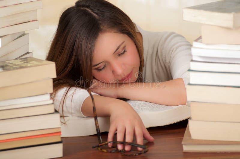 Κουρασμένος ύπνος σπουδαστών εντελώς πέρα από τα βιβλία στη βιβλιοθήκη στοκ εικόνα