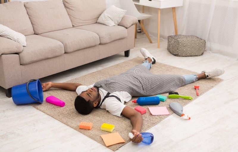 Κουρασμένο άτομο που βρίσκεται στον τάπητα που περιβάλλεται με τον καθαρισμό των προμηθειών στοκ φωτογραφίες