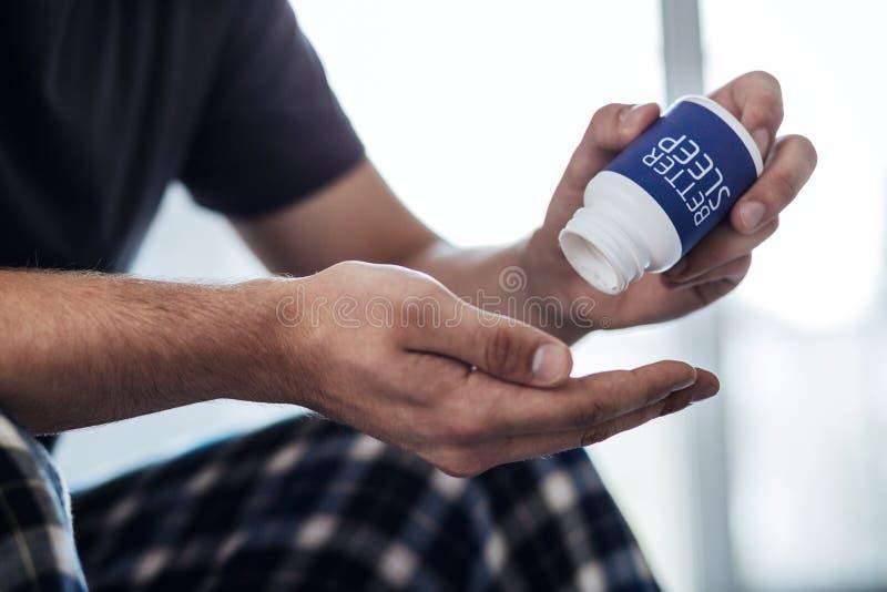 Κουρασμένο άτομο που κρατά ένα αποτελεσματικό φάρμακο στοκ φωτογραφία