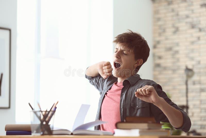 Κουρασμένο αγόρι εφήβων που κάνει την εργασία στο σπίτι στοκ εικόνες με δικαίωμα ελεύθερης χρήσης
