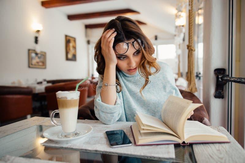 Κουρασμένο κορίτσι σπουδαστών στα γυαλιά που διαβάζει την επιστημονική λογοτεχνία στοκ εικόνα