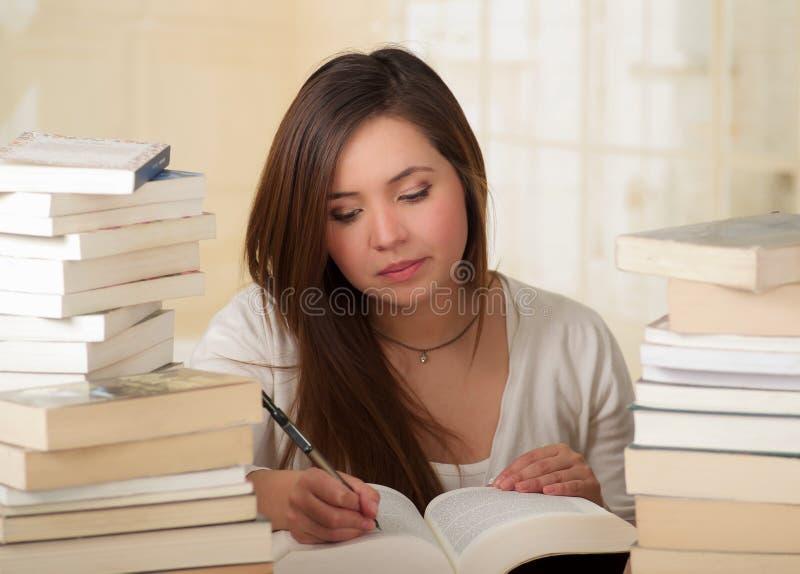 Κουρασμένο κορίτσι σπουδαστών που γράφει και που πέφτει κοιμισμένο με τα βιβλία στη βιβλιοθήκη στοκ εικόνες
