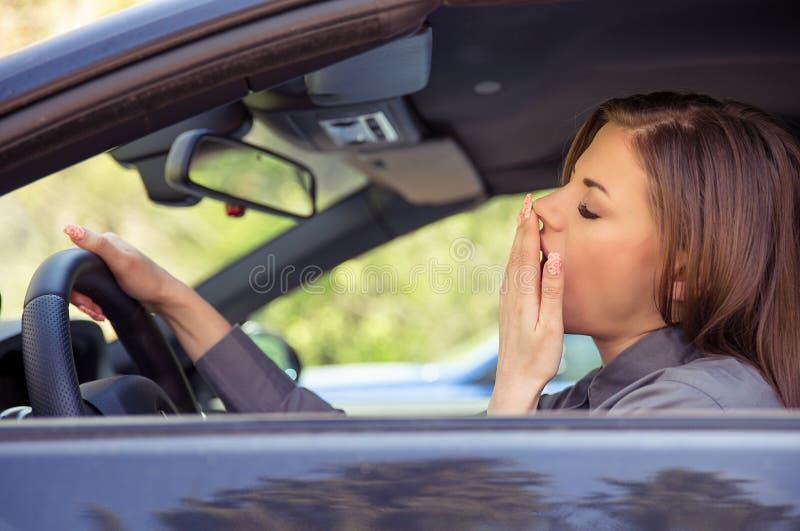 Κουρασμένο νέο οδηγώντας αυτοκίνητο γυναικών στοκ εικόνες