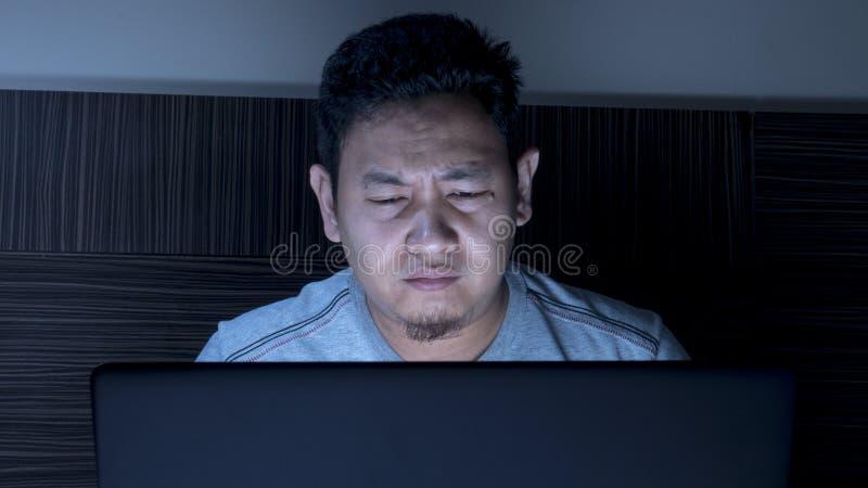 Κουρασμένο νυσταλέο άτομο που εργάζεται στο lap-top μέχρι τα μεσάνυχτα στο κρεβάτι στοκ φωτογραφία με δικαίωμα ελεύθερης χρήσης