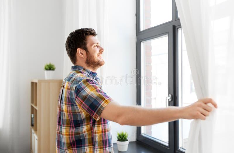 Κουρτίνα παραθύρων ανοίγματος νεαρών άνδρων στο σπίτι στοκ εικόνα με δικαίωμα ελεύθερης χρήσης