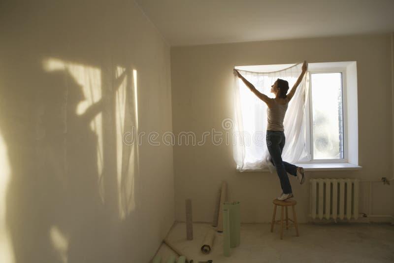 Κουρτίνα συναρμολογήσεων γυναικών στο νέο διαμέρισμα στοκ φωτογραφία με δικαίωμα ελεύθερης χρήσης