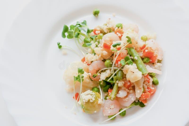 Κουσκούς με τα λαχανικά, τις γαρίδες και το ραδίκι σε ένα άσπρο πιάτο στοκ εικόνες