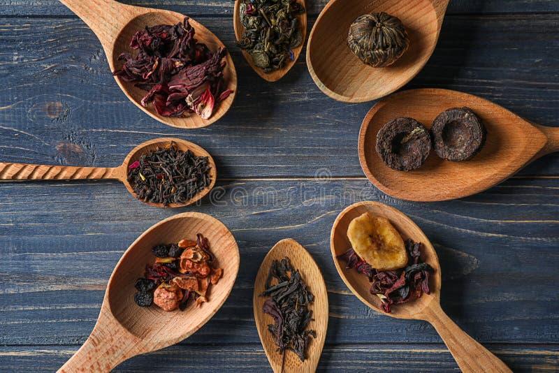 Κουτάλια με τους διαφορετικούς τύπους ξηρών φύλλων τσαγιού στο ξύλινο υπόβαθρο στοκ εικόνες με δικαίωμα ελεύθερης χρήσης