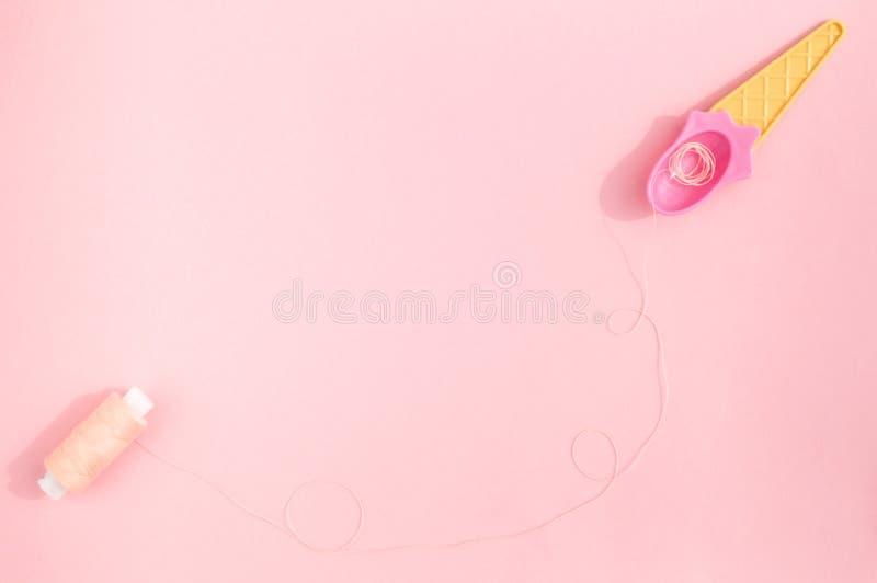 Κουτάλι θερινού ρόδινο παγωτού και χρωματισμένα κρητιδογραφία νήματα στο ρόδινο υπόβαθρο στοκ εικόνες
