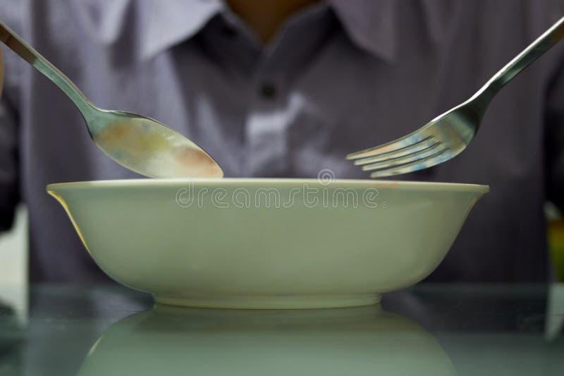 Κουτάλι και δίκρανο λαβής χεριών με το κύπελλο για να φάει το cerial πρόγευμα στοκ φωτογραφία