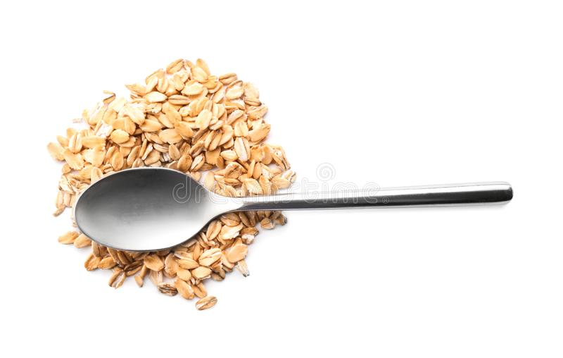 Κουτάλι και σωρός ακατέργαστο oatmeal στο άσπρο υπόβαθρο στοκ φωτογραφία