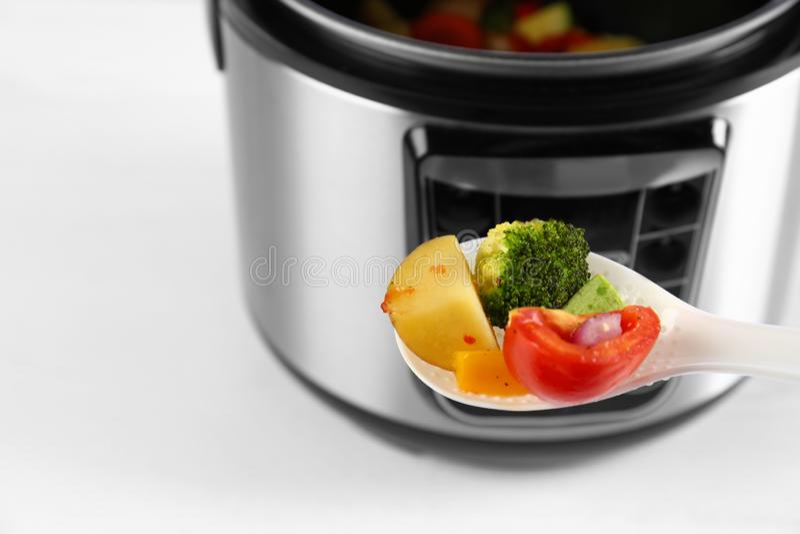 Κουτάλι με τα λαχανικά και τη θολωμένη άποψη της σύγχρονης πολυ κουζίνας στο υπόβαθρο, κινηματογράφηση σε πρώτο πλάνο στοκ εικόνες