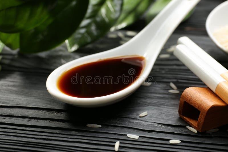 Κουτάλι με τη νόστιμη σάλτσα σόγιας στον ξύλινο πίνακα, στοκ φωτογραφία