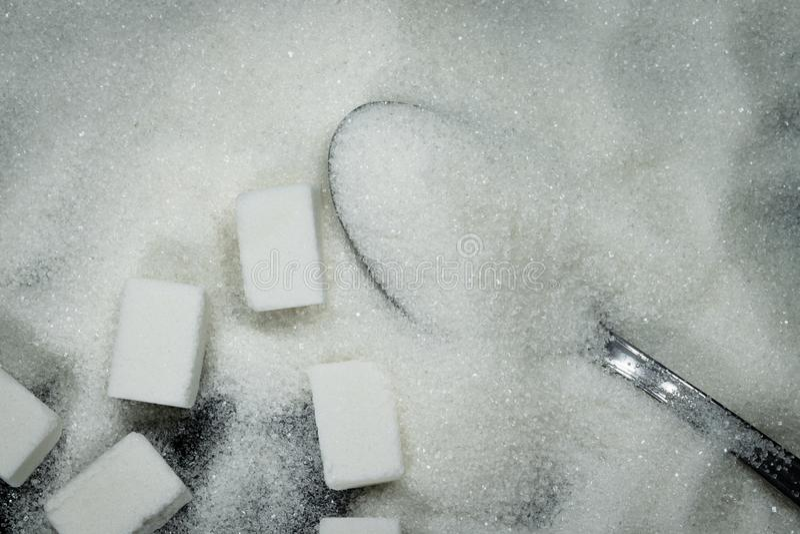 Κουτάλι σε έναν σωρό της ζάχαρης και των κύβων ζάχαρης εκτός από στοκ εικόνες με δικαίωμα ελεύθερης χρήσης