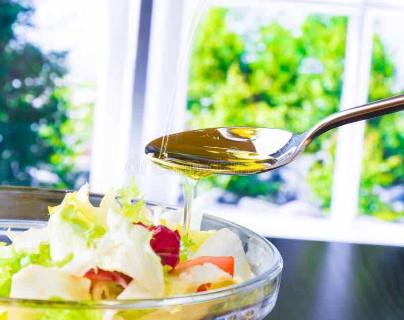 Κουτάλι με την έκχυση του ελαιολάδου στην ιταλική φρέσκια σαλάτα στοκ εικόνα
