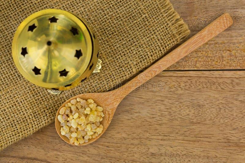 Κουτάλι της αρωματικής κίτρινης γόμμας ρητίνης δίπλα στον καυστήρα θυμιάματος ορείχαλκου στοκ φωτογραφία με δικαίωμα ελεύθερης χρήσης