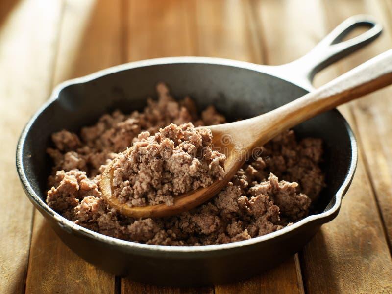 Κουταλιά του πρόσφατα μαγειρευμένου επίγειου βόειου κρέατος από το skillet σιδήρου στοκ εικόνες