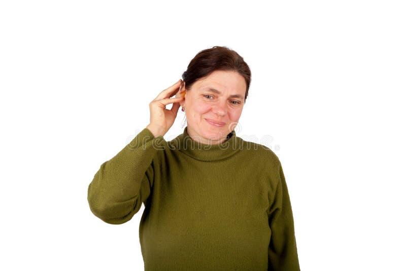 Κουφή γυναίκα που παρεμβάλλει την ενίσχυση ακρόασής της στοκ εικόνες