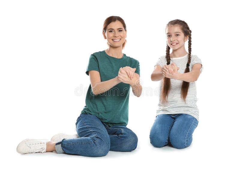 Κουφή μητέρα και το παιδί της που μιλούν με τη βοήθεια της γλώσσας σημαδιών στο λευκό στοκ εικόνα με δικαίωμα ελεύθερης χρήσης