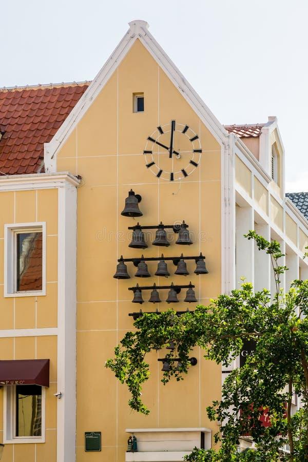 Κουδούνια και ρολόι στην κίτρινη εκκλησία του Κουρασάο στοκ εικόνες