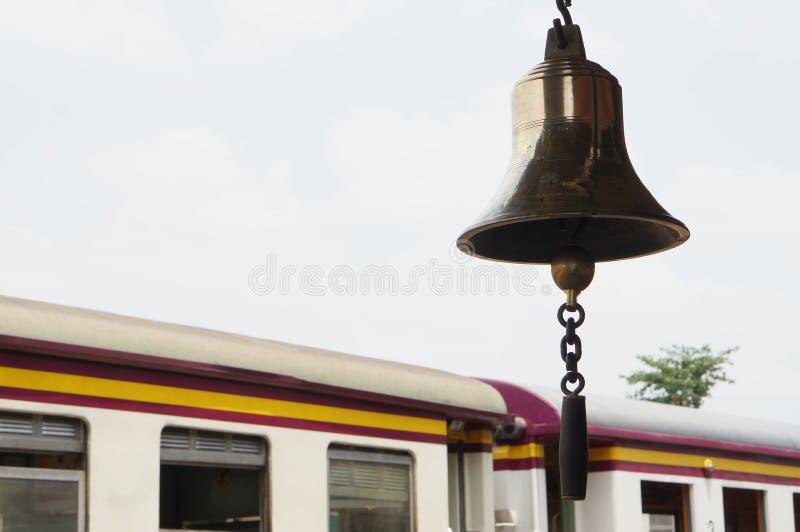 Κουδούνι στο σταθμό τρένου στο υπόβαθρο βαγονέτων στοκ φωτογραφία