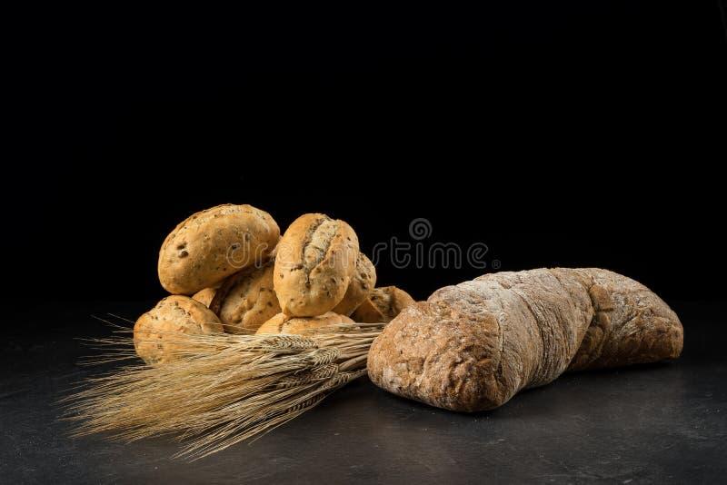 Κουλούρια και ciabatta, ψωμί στο σκοτεινό ξύλινο πίνακα Κριθάρι και φρέσκα μικτά ψωμιά που απομονώνονται στο μαύρο υπόβαθρο στοκ φωτογραφίες με δικαίωμα ελεύθερης χρήσης